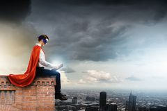Superman with book. Superman in cape and mask sitting on top of building and reading book Stock Image
