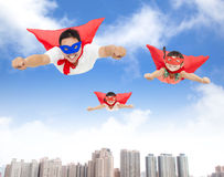 Superman and daughters  flying in the sky. With buildings background Stock Photography