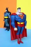 Superman en Batman op pastelkleurenachtergrond Stock Afbeeldingen