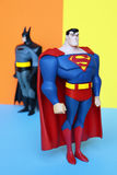 Superman et Batman sur le fond de couleurs en pastel Images stock