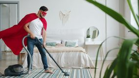 Superman in fluttering cape and mask standing in room with vacuum cleaner