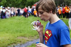 Superman icon and young man inflates a bubble. Zaporizhzhya, Ukraine May 30, 2015: feast of protection of families and children in the city park Oak grove stock image