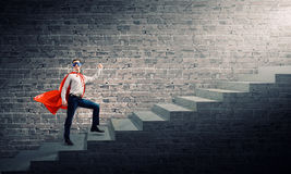 Superman on ladder. Young superman walking up the stair case Royalty Free Stock Photo