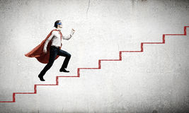 Superman on ladder. Young superman walking up the stair case royalty free stock image