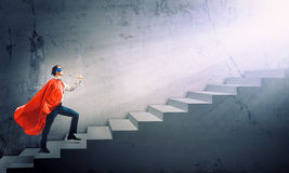 Superman on ladder. Young superman walking up the stair case Stock Photography