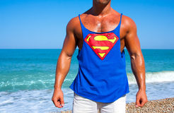 Superman. Muscular brutal man on the beach in a T-shirt with the logo of Superman royalty free stock photo