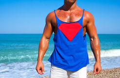 Superman. Muscular brutal man on the beach in a T-shirt with the logo of Superman stock photography