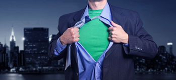 Superman in the night city. Superman on the background of night city breaks his shirt Stock Photo