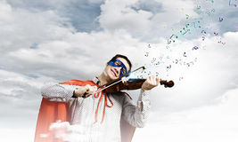 Superman playing violin Royalty Free Stock Images