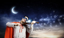 Superman playing violin Stock Images
