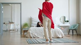 Superman in red cape running into room where woman reading book laughing. Superman in red cape and mask is running into room where young woman is reading book stock video footage