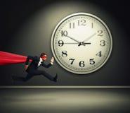 Superman running against big white clock. Serious businessman wearing like superman running against big white clock in dark room stock photo