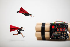 Superman and superwoman hurry to defuse the bomb. Over light grey background Royalty Free Stock Photo