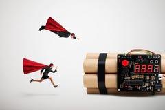 Supermann und Superwoman beeilen sich, um die Bombe zu entschärfen lizenzfreies stockfoto