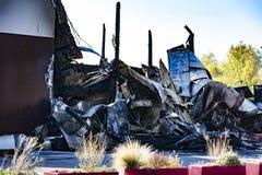 Supermarché endommagé après le feu d'incendie criminel avec des débris de brûlure de structure métallique tordue après la combust photographie stock libre de droits