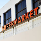 Supermarket. Entrance to supermarket with red signboard close-up Royalty Free Stock Photo