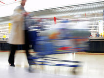 At the Supermarket. Woman with cart in motion at the grocery store stock photography