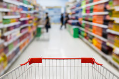 Supermarket Aisle with beverage product Shelves blur background. Shopping cart view in Supermarket Aisle with beverage product Shelves in blurry for background royalty free stock photos