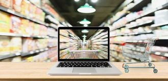 Supermarket aisle blurred background with laptop computer. And cart on wood table online shopping concept stock photo
