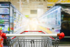 Supermarket aisle. With empty red shopping cart Royalty Free Stock Image
