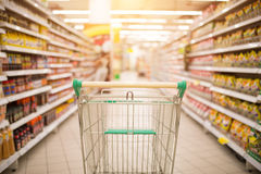 Supermarket aisle with empty red shopping cart. With customer defocus background Royalty Free Stock Image
