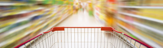 Supermarket aisle with empty red shopping cart Royalty Free Stock Images