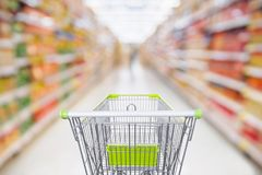Supermarket aisle with empty shopping cart at grocery store. Retail business concept Royalty Free Stock Image