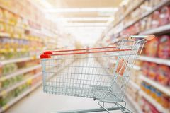 Supermarket aisle with empty shopping cart at grocery store. Retail business concept Stock Image