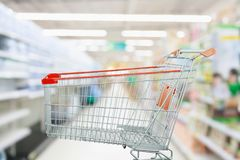Supermarket aisle with empty shopping cart at grocery store. Retail business concept Stock Photo