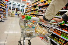 Supermarket Aisle. A Shopper Pushes a Trolley along a Supermarket Aisle - Image has a Shallow Depth of Field stock photo