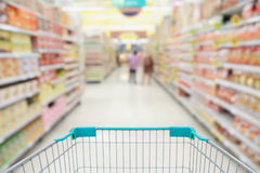 Supermarket aisle. With shopping cart royalty free stock image
