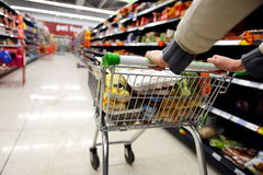 Supermarket Aisle and Trolley. London, UK - August 18, 2014: A shopper pushes a trolley along an aisle in an Asda supermarket. American company Walmart owns Asda stock photography
