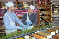 Supermarket assistants talking in front delicatessen counter. Supermarket assistants talking in front of delicatessen counter stock images