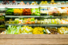 Supermarket blur background. Wood floor and Supermarket blur background.Product shelf vegetables royalty free stock photography