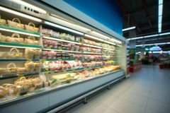 Supermarket blurred background with colorful shelves and unrecognizable customers.  royalty free stock photo
