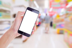 Supermarket blurred for background. Hand holding mobile smart phone on Supermarket blur background,Concept for sell shop on mobile phone stock photo