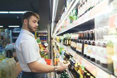 A supermarket buyer takes beer out of shelves. man got full hands of the beer while shopping. A supermarket buyer takes beer out of shelves. The man got full Royalty Free Stock Image