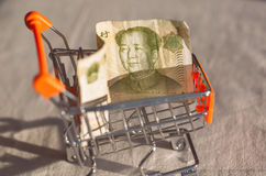 Supermarket cart with a banknote of Chinese Yuan and face of Mao, as a symbol of the modern international economy Stock Photography