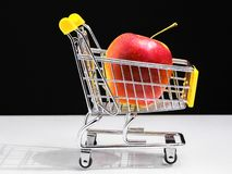 Supermarket cart concept of healthy eating. red apple.  royalty free stock image