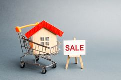 Supermarket cart with houses and a Sale Poster. The concept of selling a home, real estate services or buying from the owner. Buying and selling real estate royalty free stock images