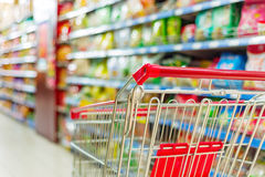 Supermarket cart. Supermarket interior, empty red shopping cart Stock Photo