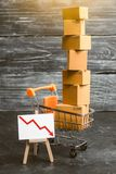 A supermarket cart loaded with lots of boxes and a red down arrow. The concept of sales drop, decrease of consumer ability royalty free stock images