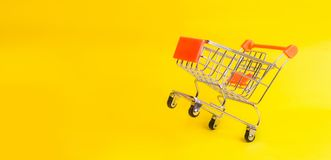 The supermarket cart stands on a yellow background. The concept of shopping and marketing, commerce and trade. The buying mood of. People. Statistical data stock photo