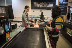 Women at supermarket check-out. A customer hands over cash to pay for items purchased at a supermarket to the check-out assistant royalty free stock images