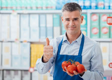 Supermarket clerk holding tomatoes Royalty Free Stock Images