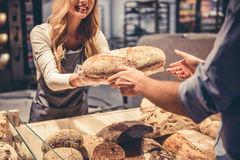 At the supermarket. Cropped image of beautiful young female worker offering a bread to the customer and smiling Royalty Free Stock Photos