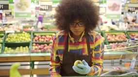 Supermarket employee african american woman with an afro hairstyle sorts the fruit. Supermarket employee african american woman with an afro hairstyle in glasses stock video footage