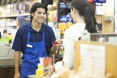 Supermarket Employee Assisting Female Customer. Supermarket employee in blue apron assisting female customer Stock Images