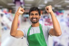 Supermarket employee holding fists up as cheerful gesture. Happy indian male supermarket or hypermarket employee holding both hands with fists up as cheerful for royalty free stock photography