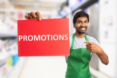 Supermarket employee holding promotions text on paper royalty free stock photography